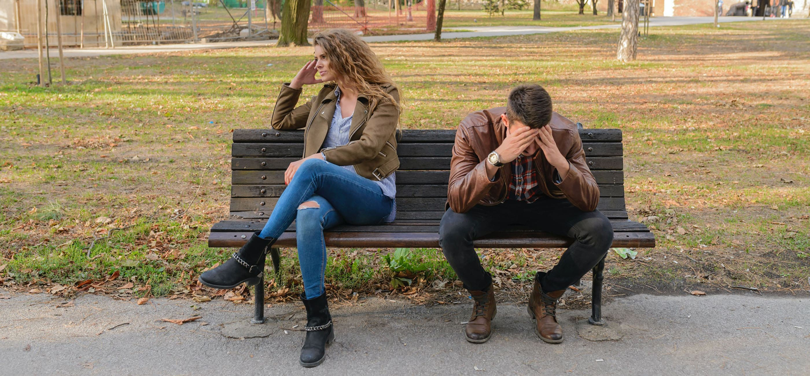 Woman and man sitting on park bench having a fight