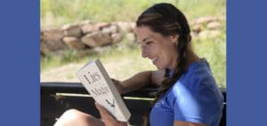 Woman smile reading Lies of the Magpie