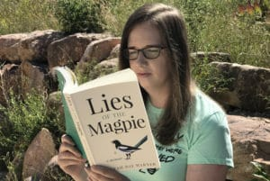 Woman reading the memoir Lies of the Magpie