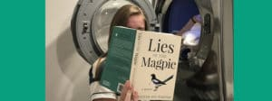 Woman reads Lies of the Magpie while doing laundry