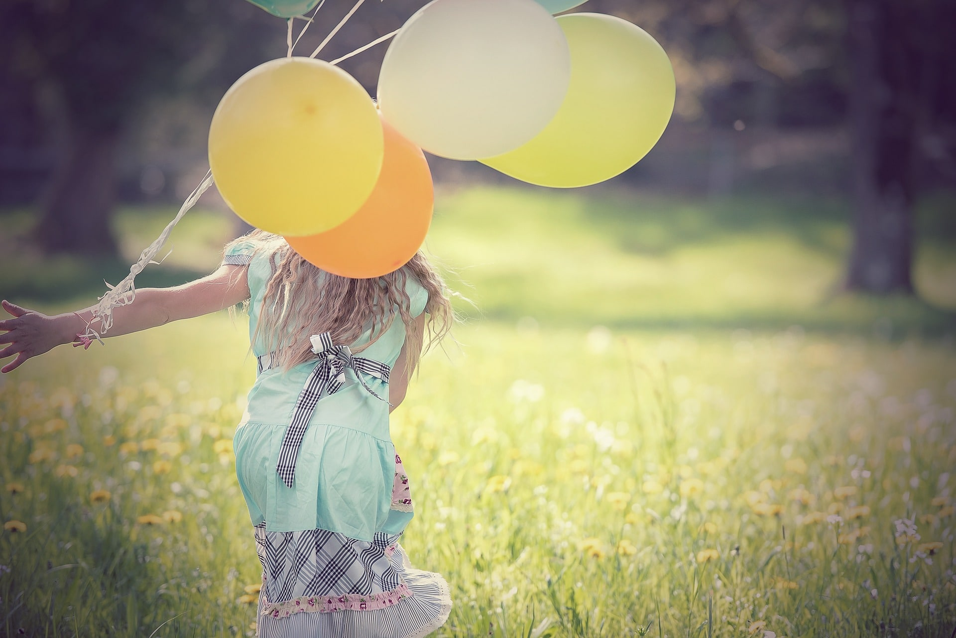 Girl running in field with balloons