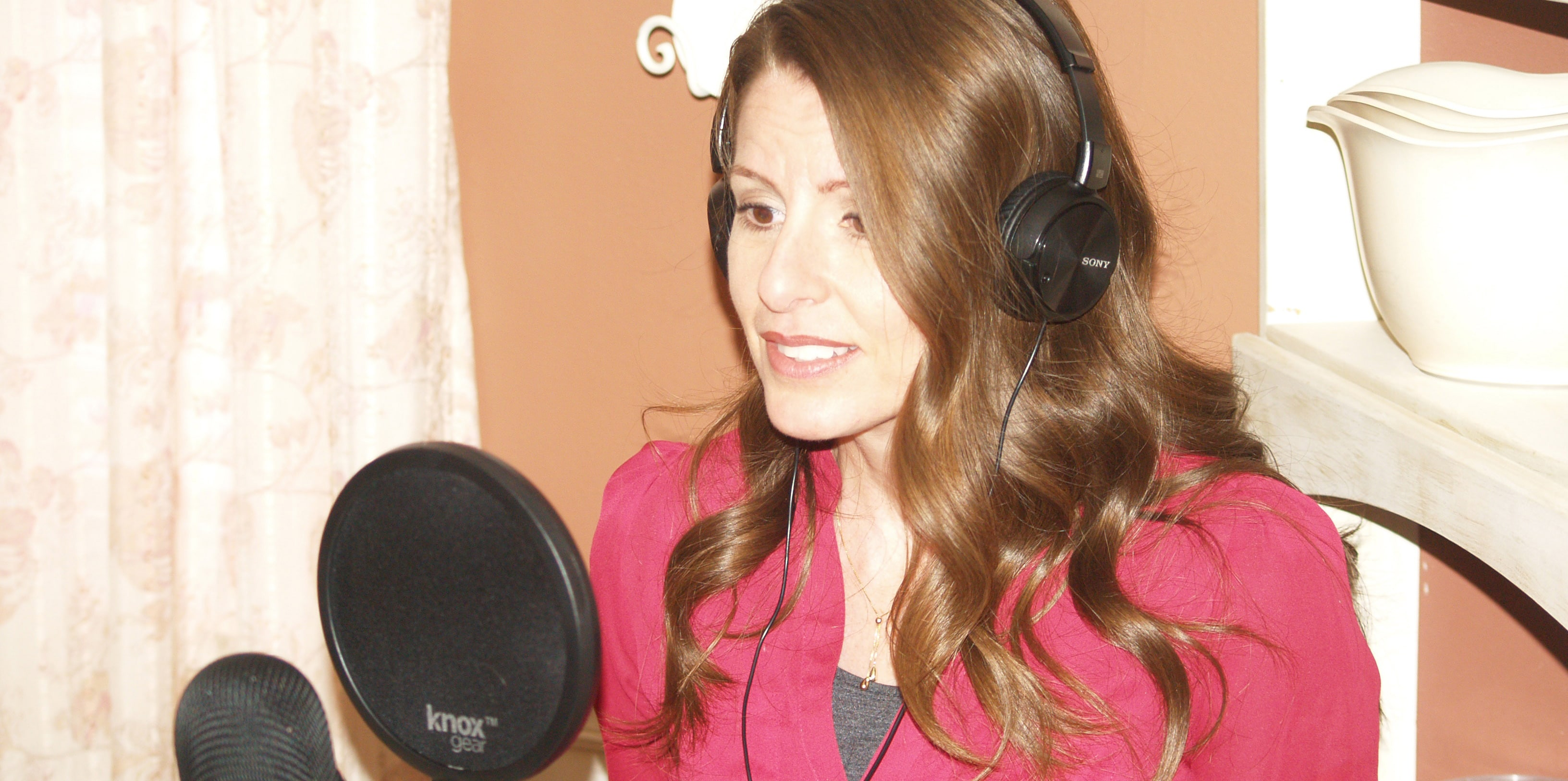 Woman with headphones talking into microphone